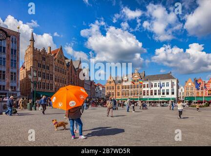 25 September 2018: Bruges, Belgium - Tour guide under orange umbrella in the centre of the city, in Markt Square, on a sunny, autumn day with gloriou - Stock Photo
