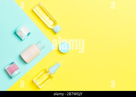 Top view of different cosmetic bottles and container for cosmetics on yellow and blue background. Flat lay composition with copy space. - Stock Photo