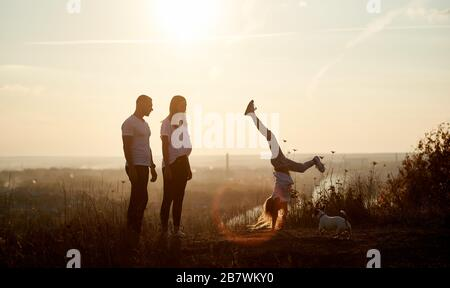 Mother and father are standing on the hill and watching their daughter doing a handstand, behind them beautiful view horizon of a setting sun