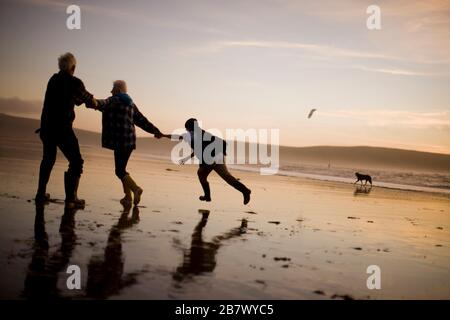 Mature adult couple being pulled by their teenage grandson along a beach at sunset.