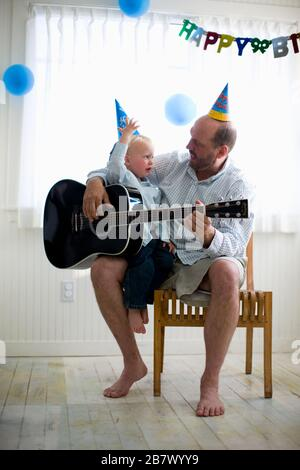 A man playing guitar with his young son - Stock Photo
