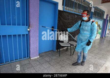 Gaza, Palestine. 18th Mar, 2020. Palestinian health workers wearing a protective facemasks are pictured in the courtyard of a United Nations Relief and Works Agency for Palestinian Refugees (UNRWA) school wearing protective gear disinfect to help prevent the spread of the new coronavirus, at Khan Youns refugee camp in southern Gaza on Wednesday on March 18, 2020, as preperations are underway to receive, examine and isolate potential victims of the Covid-19 coronavirus. So far Gaza have not confirmed any infections. But doctors in many cases believe the virus has arrived and fear that a lack of - Stock Photo