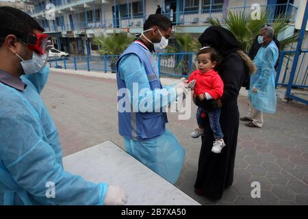 Gaza, Palestine. 18th Mar, 2020. A Palestinian health worker wearing a protective facemas disinfect child and his mother to help prevent the spread of the new coronavirus, in school at Khan Youns refugee camp in southern Gaza on Wednesday on March 18, 2020, as preperations are underway to receive, examine and isolate potential victims of the Covid-19 coronavirus. So far Gaza have not confirmed any infections. But doctors in many cases believe the virus has arrived and fear that a lack of disease surveillance systems - shortages of tests, basic supplies and properly trained professionals - is a - Stock Photo