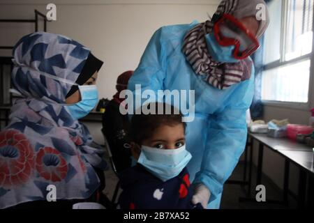 Gaza, Palestine. 18th Mar, 2020. A Palestinian doctor wearing a protective facemask checks the body temperature of a child at a United Nations Relief and Works Agency for Palestinian Refugees (UNRWA) school at Khan Youns refugee camp in southern Gaza on Wednesday on March 18, 2020, as preperations are underway to receive, examine and isolate potential victims of the Covid-19 coronavirus. So far Gaza have not confirmed any infections. But doctors in many cases believe the virus has arrived and fear that a lack of disease surveillance systems - shortages of tests, basic supplies and properly tra - Stock Photo