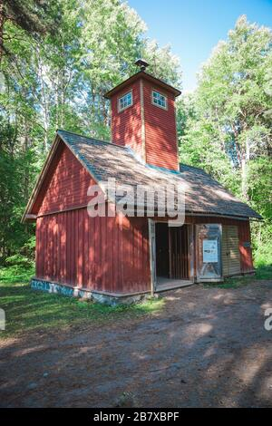 Traditional Red Estonian Wooden House in the middle of a forest - Stock Photo