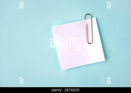 Paper sheet with a paper clip flat lay, copy space - Stock Photo