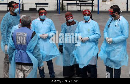 Gaza, Palestine. 18th Mar, 2020. Palestinian health workers wearing a protective facemasks are pictured in the courtyard of a United Nations Relief and Works Agency for Palestinian Refugees (UNRWA) school at Khan Youns refugee camp in southern Gaza on Wednesday on March 18, 2020, as preperations are underway to receive, examine and isolate potential victims of the Covid-19 coronavirus. So far Gaza have not confirmed any infections. But doctors in many cases believe the virus has arrived and fear that a lack of disease surveillance systems - shortages of tests, basic supplies and properly train - Stock Photo