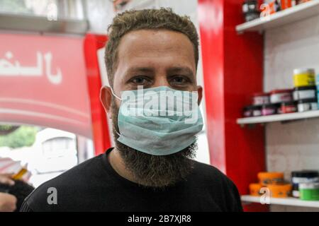 Gaza, Palestine. 18th Mar, 2020. A barber salon in the Jabalia refugee camp in Gaza adopting preventive measures against the spread of the coronavirus. Barbers in the shop wear protective masks, sterilize all their tools, and provide hand sanitizer, as part of coronavirus precautions. Although no cases have been reported so far in the Gaza strip, it is believed that it may be due to the lack of testing kits in the Palestinian enclave. The blockaded Gaza Strip is an extremely poor territory with a collapsing health system lacking in basic infrastructure and medical supplies. The Credit: ZUMA Pr - Stock Photo