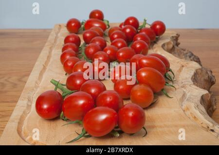 Tomatoes on a vine in a kitchen setting - Stock Photo