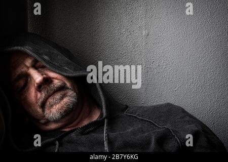 A middle aged man in a fatigued state whilst suffering from depression. Stock Photo
