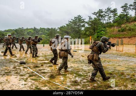 U.S. Marines with 1st Battalion, 6th Marine Regiment, conduct marksmanship drills on Camp Schwab, Okinawa, Japan, March 13, 2020. One of the drills Marines utilize to maintain their lethality involves firing at close ranges as well as gradual movements towards a target to simulate closing with the enemy. This drill is being executed by an activated reserve unit currently attached to 3rd Marine Division as part of the unit deployment program. (U.S. Marine Corps photo by Lance Cpl. Ujian Gosun) - Stock Photo