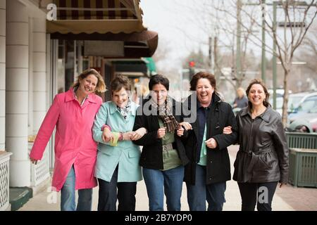 Middle aged women walking and laughing wtih linked arms - Stock Photo