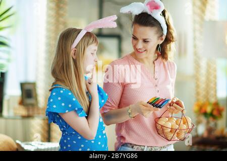 pensive elegant mother and child in easter bunny ears holding basket with farm eggs and food coloring in the modern living room in sunny spring day. - Stock Photo