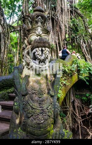 Foreign tourists cross a bridge with a dragon carving in the Sacred Monkey Forest, Ubud, Bali - Stock Photo