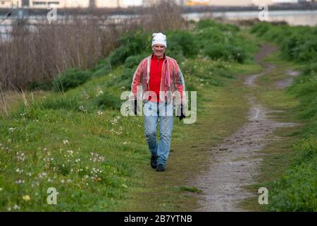 A man takes a walk in Corte Madera Marsh State Marine Park and meets a dog. - Stock Photo