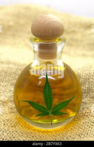 Hemp products - Cannabis seed oil in the glass bottle with the cannabis leaf on the cannabis fabric - Stock Photo