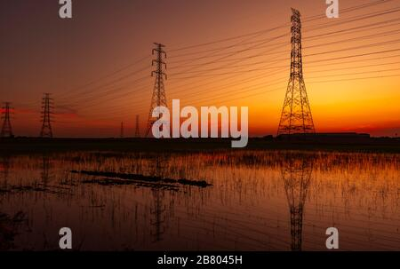 High voltage electric pylon and electrical wire with sunset sky. Electricity poles. Power and energy concept. High voltage grid tower with wire cable Stock Photo