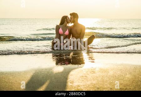 Young couple in love kissing on the beach at sunset - Two lovers having tender moments in summer vacation - Romantic concept - Soft focus on them - Wa - Stock Photo