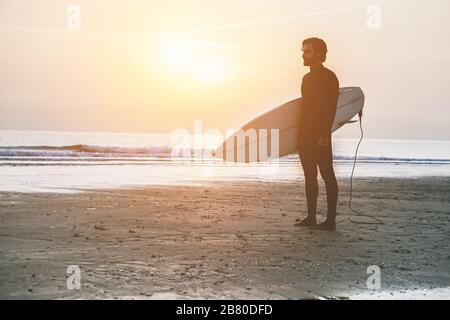 Silhouette of surfer standing on the beach waiting for waves at sunset time - Man with surfboard wearing wet suit looking sunrise - Extreme sport conc - Stock Photo
