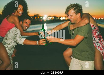 Happy friends drinking beer and having fun on the beach after sunset - Young people enjoying summer vacation - Youth,holidays,party and friendship con - Stock Photo