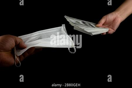 Close up Sell buy medical face mask, Hand holding doctor masks virus protection and money of 100 US dollars banknote a lot of at black background, It - Stock Photo