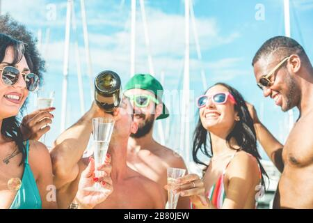 Happy friends drinking champagne in summer boat party - Young millennials people having fun dancing and laughing together - Youth lifestyle and vacati