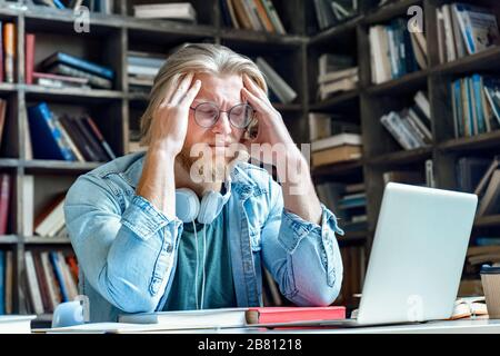 Young stressed tired man in glasses with closed eyes massage head. - Stock Photo
