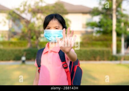 Covid-19 Coronavirus epidemic virus symptoms and Air pollution pm2.5 concept.Little Asian girl wearing mask for protect pm2.5 and show stop hands gest - Stock Photo