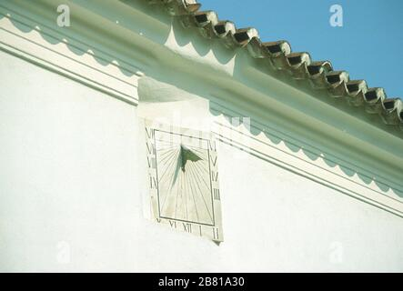 Sundial with Roman numerals, mounted high up on the white, stone wall of a building in Parga, Preveza, Epirus, Greece. The tiled roof above casts a shadow on the wall. - Stock Photo