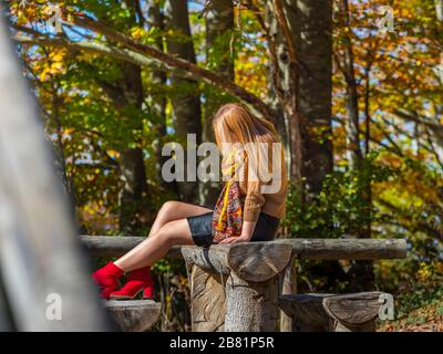 Stalking alone lonesome teen girl aka young woman outdoors outside in nature natural environment park - Stock Photo