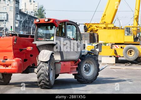 Constuction site heavy machinery industrial background. Telescopic handler vehicle and big mobile crane working at city building development - Stock Photo