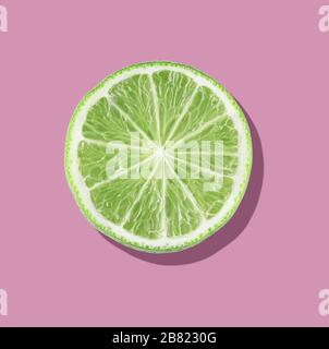 Green lime slices on vibrant pink color background. Minimal summer concept. flat lay food texture - Stock Photo