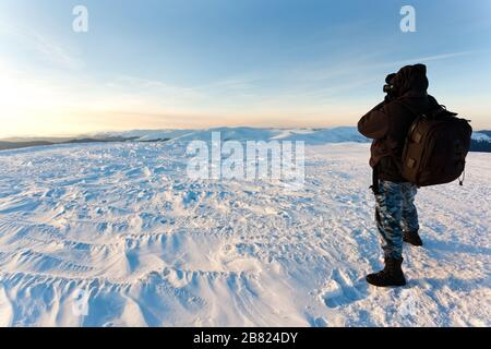 Young man photographer in winter clothing standing and making photo with camera in sunlight with white snow background. Travelling and making photos o - Stock Photo