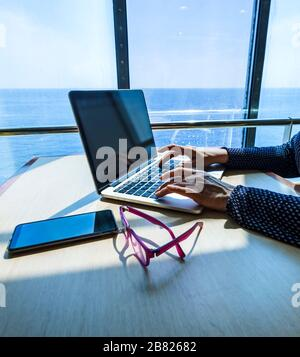 Woman using laptop computer, searching the web, browsing information while traveling on a ship