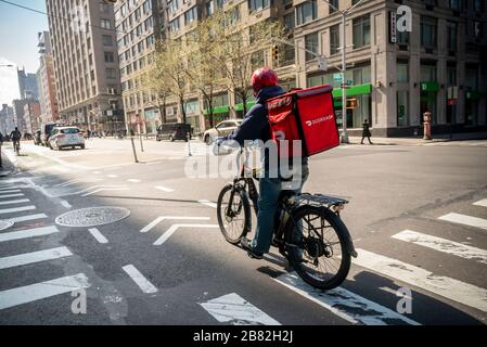 A delivery person with a DoorDash branded tote on his bicycle in the Chelsea neighborhood of New York on Friday March 13, 2020. (© Richard B. Levine) - Stock Photo