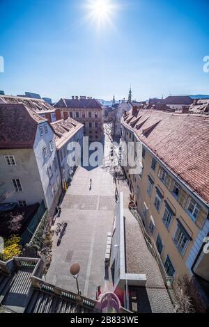 View from hill Schlossberg to empty place Schlossbergplatz in deserted town Graz, Styria at virus quarantine in Spring, Austria - Stock Photo