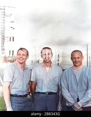 NASA's Apollo 11 flight crew, Neil A. Armstrong, Michael Collins, and Buzz Aldrin, standing near the Apollo/Saturn V at Kennedy Space Center in Florida, July 16, 1969. Image courtesy National Aeronautics and Space Administration (NASA). Note: Image has been digitally colorized using a modern process. Colors may not be period-accurate. () - Stock Photo
