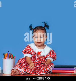 Cute one year old mixed race Asian Caucasian german girl wearing red dress smiles sweetly looking at the camera on blue background - Stock Photo