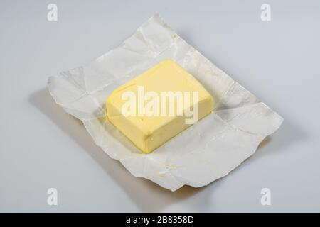 The wrapped butter is open for proper nutrition with amino acids for the normal functioning of the heart and itelect - Stock Photo