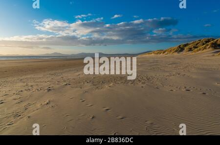 Views along the beach with sand dunes and mountains in the distance, Harlech, North Wales - Stock Photo