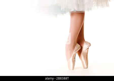 Legs of ballerina woman in white tutu and pointe shoes over white background. Ballet, grace, beauty, art concept - Stock Photo