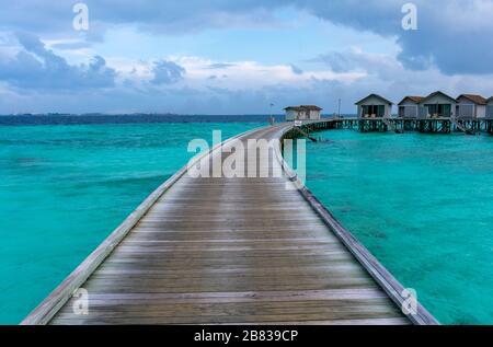 North Malé Atoll, Maldives - December 29 2019 - A wooden pier towards the water villas