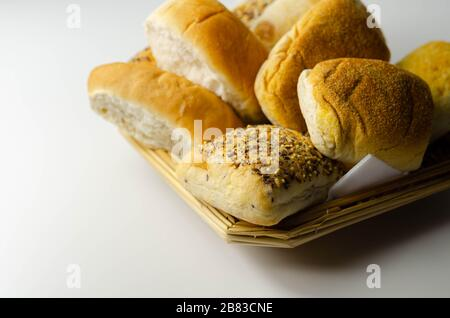 Various types of bread served on a wicker tray, delicious and fresh rolls, morning food - Stock Photo