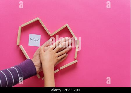 Hand of a father and child stacked on top of each other inside a heart shape made of wooden pegs. Over pink background with Family sign. - Stock Photo