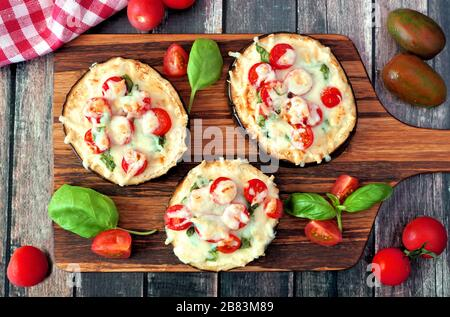 Healthy eggplant mini pizzas with melted mozzarella, tomatoes and basil on a serving board against rustic wood - Stock Photo