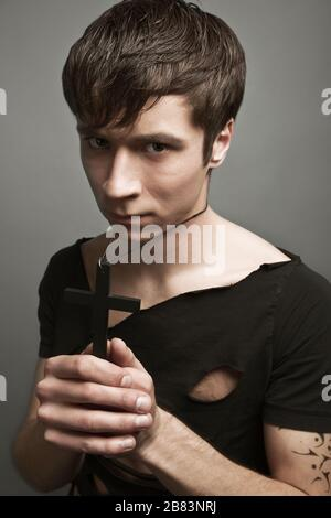 Young man in modern black clothing and freedom tattoo holding big black cross in hands with eyes closed. - Stock Photo