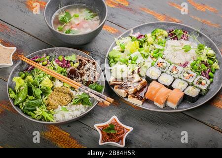 Close up pan-Asian dishes in bowls. Rice with spices and beef, salad with beans, rolls with salmon and avocado, fish soup. Tasty and healthy nutrition - Stock Photo