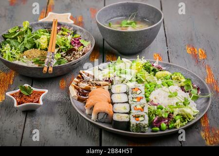 Pan-Asian dishes in bowls. Rice with spices and beef, salad with beans, rolls with salmon and avocado, fish soup. Tasty and healthy nutrition - Stock Photo