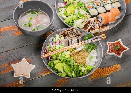 Assorted pan-Asian dishes in bowls. Rice with spices and beef, salad with beans, rolls with salmon and avocado, fish soup. Tasty and healthy nutrition - Stock Photo