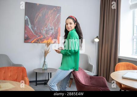 Successful woman in bright green shirt standing near an armchair.